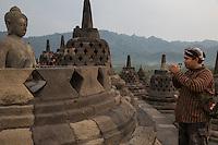 Borobudur, Java, Indonesia.  Early-morning Visitor Praying to Statue of the Buddha.