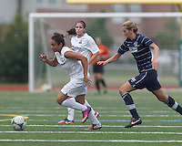 Boston Aztec forward Sonia Basma (8) dribbles as Seacoast United Phantoms player Carly Gould (3) closes. In a Women's Premier Soccer League (WPSL) match, Boston Aztec (white) defeated Seacoast United Phantoms (blue), 3-0, at North Reading High School Stadium on Arthur J. Kenney Athletic Field on on June 25, 2013.