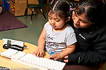 Toddler program mother and daughter playing with computer keyboard in pretend play area