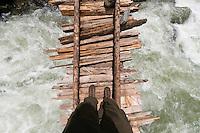 Point of view shot of trekker crossing the swollen Kanka River on a rickety wodden bridge, Naranag, Gangabal Lake region, Kashmir Himalayas, India