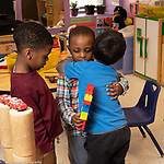 Education Preschool 3-4 year olds two boys talking about dispute while 3rd boy looks on, boys hugging in resolution