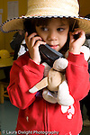 Preschool 3-5 year olds pretend play girl in dressup hat holding stuffed animal and talking on phone vertical