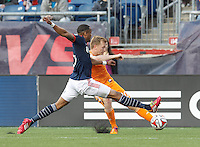 Houston Dynamo midfielder Andrew Driver (20) crosses the ball as New England Revolution substitute defender Darrius Barnes (25) defends. In a Major League Soccer (MLS) match, the New England Revolution (blue/white) defeated Houston Dynamo (orange), 2-0, at Gillette Stadium on April 12, 2014.