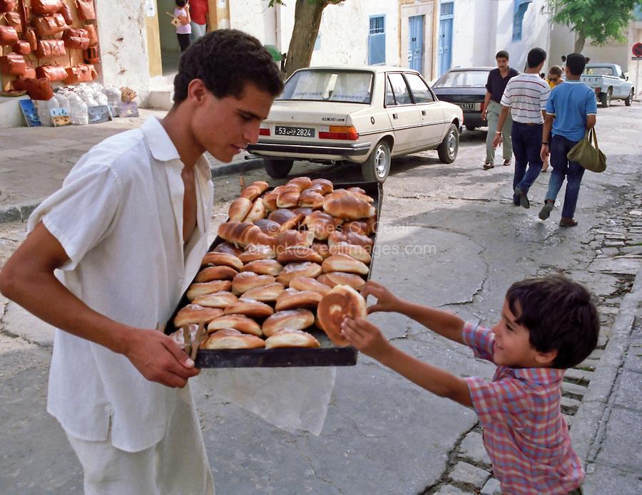 Tunisia, Sidi Bou Said.  Boy Buying a Pastry.