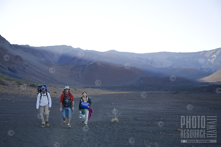 Hikers carrying backpacks and sleeping bas, walking in the Haleakala crater on Maui