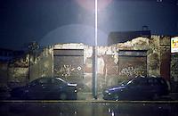 Milano, quartiere Bovisa, periferia nord. Notte piovosa. Due automobili parcheggiate in via Varè di fronte alle saracinesche e ai resti del muro di un vecchio edificio demolito. Sullo sfondo, una vecchia fabbrica da molti anni in disuso --- Milan, Bovisa district, north periphery. Rainy night. Two cars parked in Varè street in front of the shutters and the rests of the wall of an old demolished building. On the background, an old factory into disuse since many years