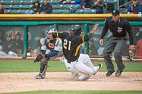 Alfredo Marte (21) of the Salt Lake Bees beats the throw to the John Baker (24) of the Tacoma Rainiers in Pacific Coast League action at Smith's Ballpark on May 7, 2015 in Salt Lake City, Utah.  (Stephen Smith/Four Seam Images)