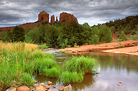 Gray rain storm clouds over Cathedral Rocks, trees, water, and grass at Red Rock Crossing, Oak Creek, Sedona, Arizona.