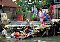 Families in Palembang Indonesia wash clothes in the Musi River. Living conditions along the river are crowded and lack modern conveniences. waterway, economic, social conditions. Family washes clothes in river. Palembang, Indonesia Asia.