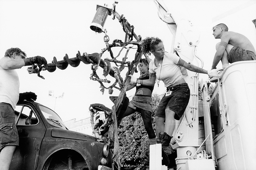 """Italy. Province of Sicily. Menfi. Mutoid Waste Company. Two stripped to the waist men and two women unloads form a truck a giant human metal sculture and the Fiat 500 which will burned during the show at """"Inycon"""" festival. Using all types of industrial scrap for their raw materials the Mutoid Waste Company are a mobile and adaptable group of performance artists. Having the necessary equipment to allow them complete freedom, they have created an entirely new form of scultural-musical performance crossing the boundaries of circus, theatre and art. © 1999 Didier Ruef"""