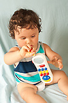 Infant development 12 month old baby boy playing with and inspecting plastic phone toy