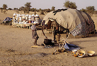 Akadaney, Central Niger, West Africa.  Fulani Nomads.  Woman with Children Preparing Dinner in front of her Sleeping Enclosure.  Food Storage and Eating Utensils on Platform in Rear.