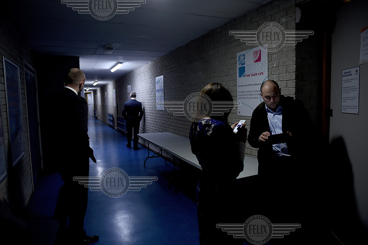 UKIP leader Nigel Farage waits in a corridor in the Carn Brae Leisure Centre in Penzance, Cornwall, before going out into the gym where he gave a speech at a public meeting, as he toured the South West on England during campaigning for the 7 May 2015 general election.