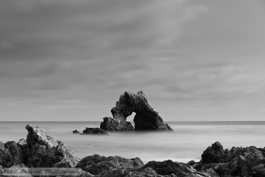 The arch rock at Little Corona seen on a cloudy evening just after sunset.  I love the soft dusk lighting illumindating the diffuse clouds overhead.  The image is a long exposure, so the ocean's waves have morphed into a silky smooth misty layer.