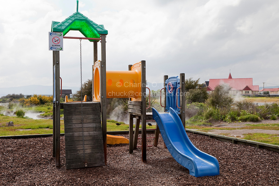 Steam Rises behind Playground Equipment, Ohinemutu Village, Rotorua, north island, New Zealand.  Underground hot springs rise to the surface throughout the settlement of Rotorua.