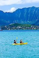 Two women set out in a kayak to explore Kaneohe Bay.  The Ko'olau mountains tower in the background.