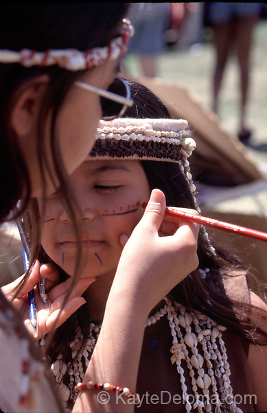 An older dancer helps apply face paint to a going girl before a performance by the Tongva Nation Dancers at the Long Beach Friendship Festival, Long Beach, CA