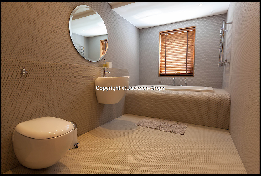 BNPS.co.uk (01202 558833)<br /> Pic: Jackson-Stops/BNPS<br /> <br /> ****Must use full byline****<br /> <br /> One of the three plush bathrooms.<br /> <br /> A stunning cliff-top house has grown into a 1.25 million pounds property after it was built on a disused allotment.<br /> <br /> Jamie and Zoe McLintock forked out £80,000 for the overgrown plot of land eleven years ago because it was atop a cliff along Devon's craggy coastline.<br /> <br /> The enterprising couple spent a further £600,000 and three years of their time building the beautiful five-bedroom pad.<br /> <br /> But they are now set to double their money after the incredible property went on the market for a whopping £1.25 million with estate agents Jackson-Stops.<br /> <br /> The white-washed three-storey house is perched on top of 100ft cliffs overlooking Tunnels Beaches in Ilfracombe, a stretch of private Victorian beach owned by the couple since 2001.