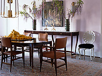 The pale pink dining room is furnished with a classical dining table, vintage Ponti dining chairs and French painted-metal shell chairs