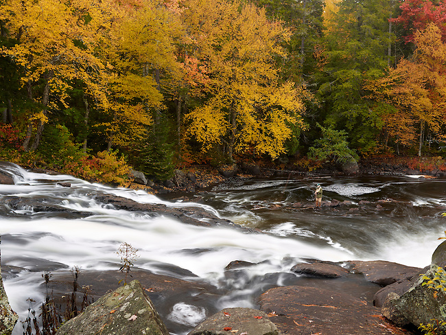 A fly fisherman tries the water at Buttermilk Falls on Long Lake Lake