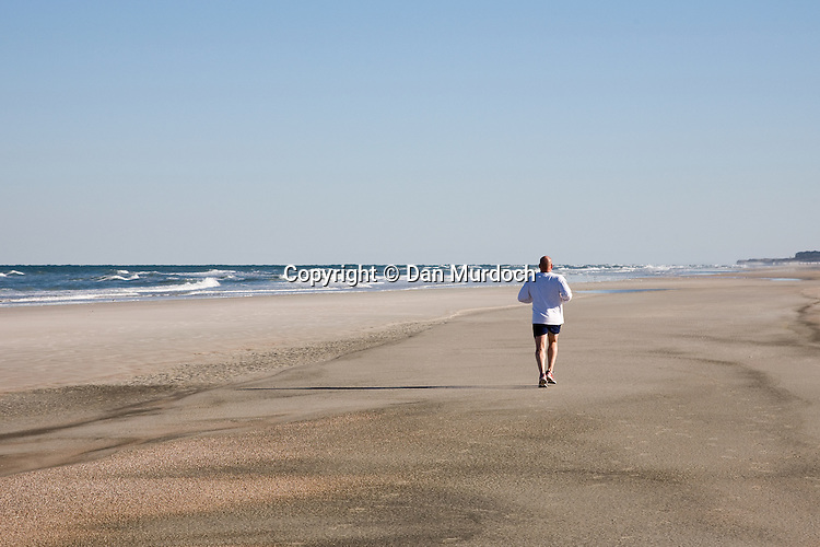 Lone jogger on Crescent Beach, St. Augustine, Florida.