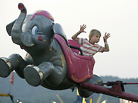 Dylan Hahn makes a funny face to friends below while riding high on the dumbo ride Thursday at the Albemarle County Fair. Photo/Andrew Shurtleff.. Albemarle County Fair  ride family fun entertainment culture.