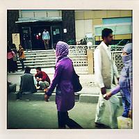 A woman wearing a vivid purple head scarf walks along a busy street.