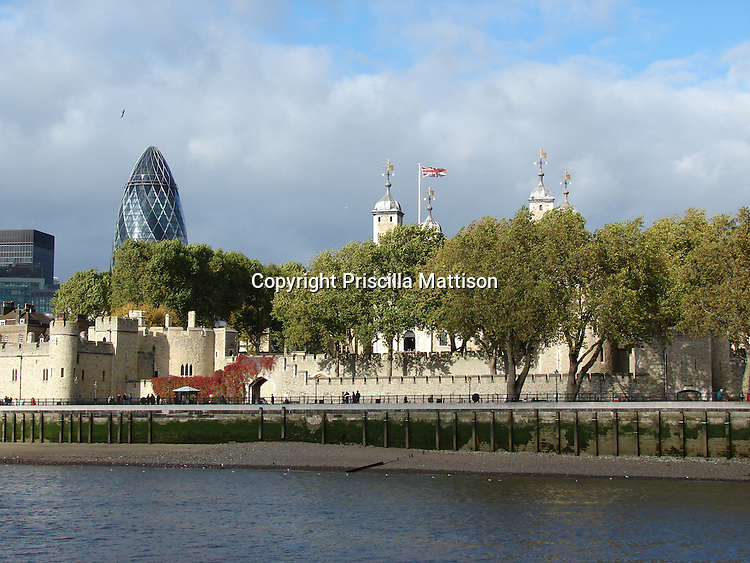 London, England - October 31, 2006:  The Tower of London and modern buildings rise near the edge of the Thames.