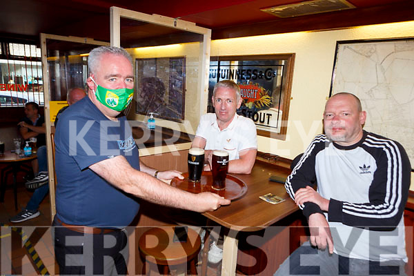 John C O'Shea delivers Denis O'Leary  centre and Ossi Fritsche their order in Jack C's pub Killarney on Monday after reopening
