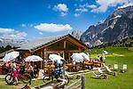 Italy, South Tyrol (Trentino - Alto Adige), Dolomites, near Selva di Val Gardena: alpine pasture hut 'La Malga Sella' with Sella Group at Sella Pass Road | Italien, Suedtirol (Trentino - Alto Adige), oberhalb von Wolkenstein in Groeden: bewirtschaftete Almhuette Malga Sella Alm vor der Sellagruppe an der Sella-Joch-Passstrasse