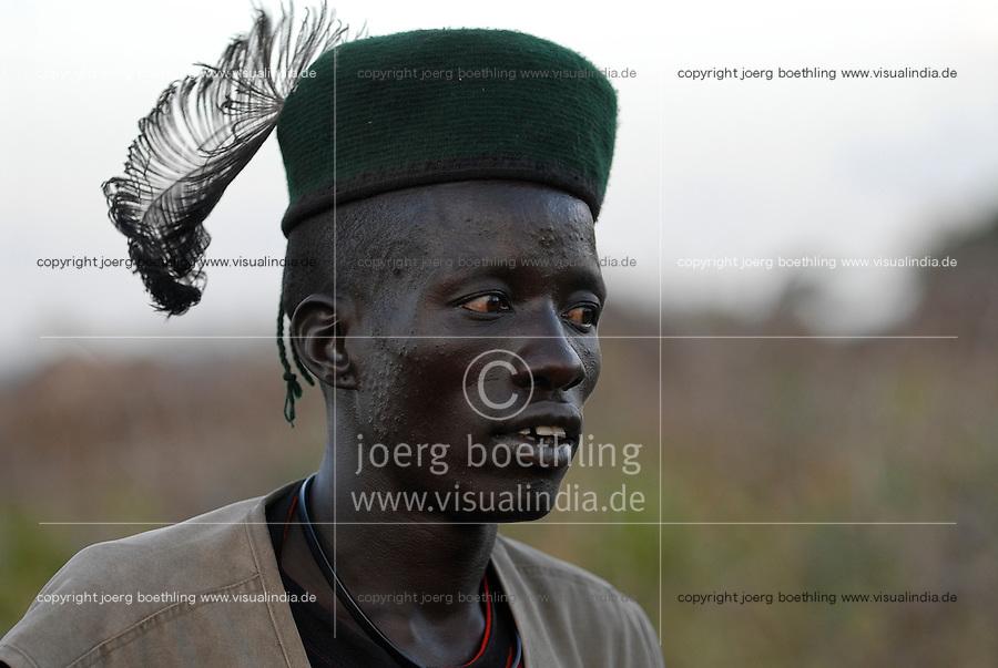 UGANDA Karamoja , Kotido, young Karimojong man in uniform shirt and hat with feather