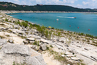 Hippie Hollow Park lies in the basin area of Lake Travis in the Hill Country of central Texas, approximately one-half hour's drive from downtown Austin. The Park features a steep, rocky shoreline and provides some spectacular views of Lake Travis. This heavily-used park, the only nudist public park in Texas, is popular for nude sunbathing and swimming.