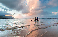 At sunset, a family enjoys the warm water of Hanalei Bay near Princeville Resort, Kaua'i.