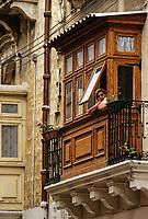 Vittoriosa, Birgu, Malta.  Woman in Balcony Window.