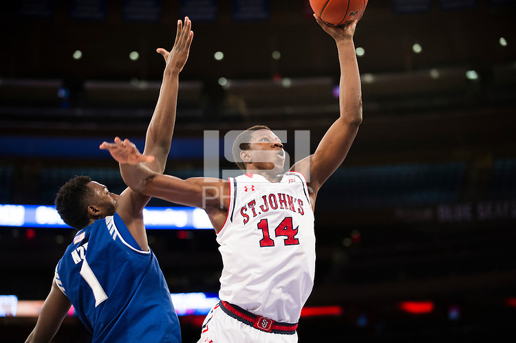 NEW YORK, NY - Sunday December 21, 2015: Kassoum Yakwe (#14) of St. John's goes up strong against Michael Nzei (#1) of Seton Hall as the two teams square off in regular season play at Madison Square Garden.