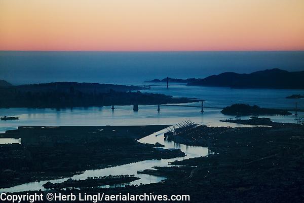 aerial photograph from Oakland Estuary toward the Golden Gate Bridge of San Francisco Bay at dusk, California