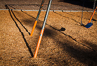 A children's swingset casts its shadow, drawing dark lines on the empty playground.
