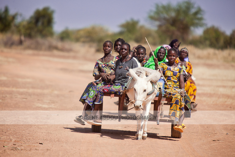 """In West Africa, certain villages have markets that """"assemble"""" at regular intervals, such as weekly or every three days.  People from villages around the region come on market day to buy and sell food, livestock, and other goods and services.  In this photo, a group of Tuareg women ride a donkey cart to the Bourro market in northern Burkina Faso."""