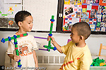 Preschool ages 3-5 two boys holding mock weapons they built from colored connecting plastic cubes horizontal