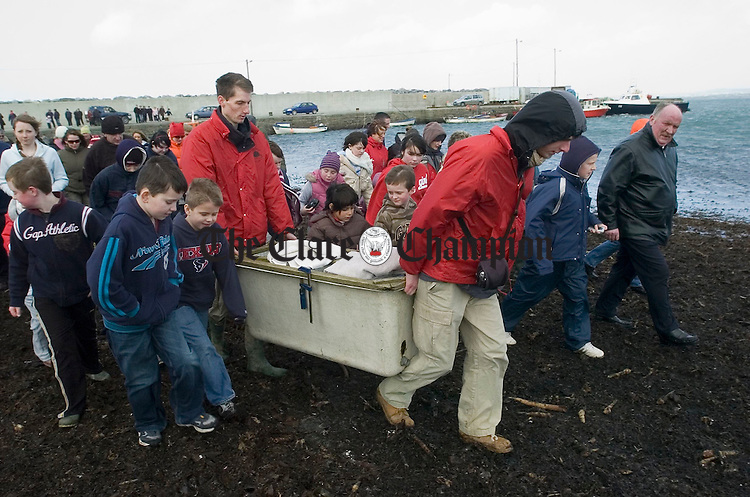 """Locals join in on the excitement as """"Kelly"""", the seal found on the road in Limerick, is carried to the beach to be released into the sea at Seafield, Quilty, by the Irish Seal Sanctuary on Sunday last. Photograph by John Kelly."""