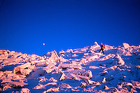 Winter climber in a high altitude landscape near the summit of Mt. Adams. Alpenglow of the setting sun casts a red glow over the rough snow cover as the moon rises above. White Mountain National Park presidential Range, New Hampshire.