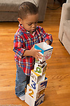 Two year old toddler boy building with cardboard stacking cubes, putting larger block on top of tower