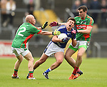 Liam Markham of  Cratloe in action against Michael Hogan and Mark Mc Carthy of Kilmurry Ibrickane during their senior football final replay at Cusack park. Photograph by John Kelly.