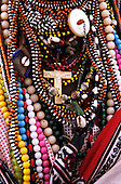 Lolgorian, Kenya. Siria Maasai woman's necklaces with masses of brightly coloured beads and a crucifix.
