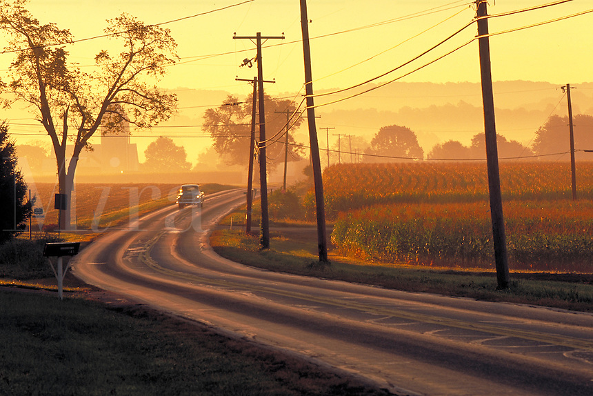 Car on country road at sunrise. Strasburg Pennsylvania USA Lancaster County.