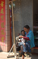 """A boy recieves medical care from a drip on the side of a street at Shabao village, the nearest large village to China's """"Space Launch Centre"""" in Sichuan Province, China. The Chinese made Long March Rocket called Chang'e 1, was launched 24th October 2007, Sichuan Province, China."""