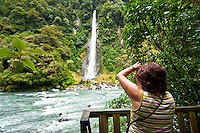 Woman taking picture of Thunder Creek Falls  and Haast River near Haast Pass - Mt. Aspiring National Park, New Zealand