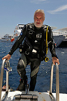 Smiling man scuba diver climbing the ladder of a diving boat off the coast of Safaga, Egypt, Red Sea (MR)