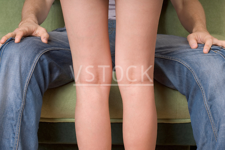 Woman standing in front of man, mid section
