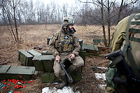 """UKRAINE, 02.2016, Oblast Donetsk. Ukrainian-Russian conflict concerning Eastern Ukraine / Foreign volunteers (""""Task Force Pluto"""") fighting with the far-right militia Pravyi Sektor against the Russian-backed separatists: Ben (Austria) sits on empty ammunition boxes behind the frontline to talk to his comrades after returning from a position close to the enemy's. © Timo Vogt/EST&OST"""